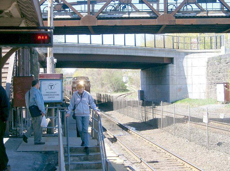 060429NatickStationPlatformAndBottomOfCRT Below the Walnut Street bridge and the Main Street bridge beyond, the start of the Cochituate Rail Trail curves off to the right.