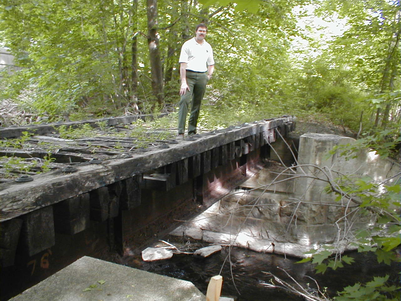 CRT bridge_oblique010514 Some improvements take major steps. In 2001, Cochituate State Park Supervisor Carey VandenAkker demonstrates the deteriorated deck of one of two railroad bridges just north of Old Connecticut Path. Creosoted timbers and crossties are heavy, and don't mix well with the trout in Cochituate Brook.