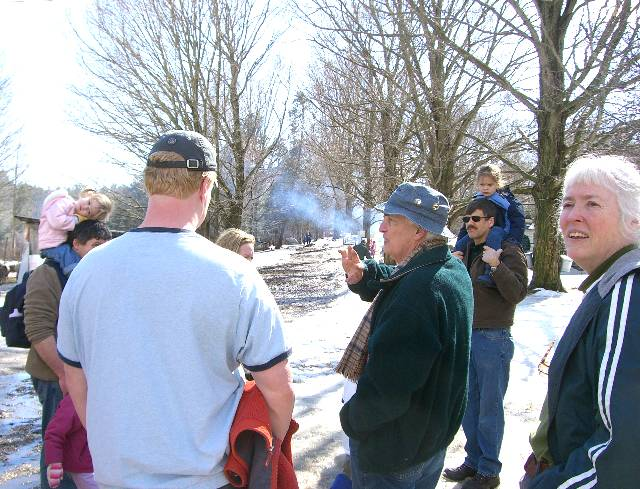 070303DaveDimmick1 Today there are lots of guests, and lots of tours. Dave Dimmick explains how the farmers would line their roads with lanes of maple trees, for easy winter access to the sap buckets.